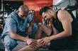 african american doctor examining injured knee of screaming sportsman
