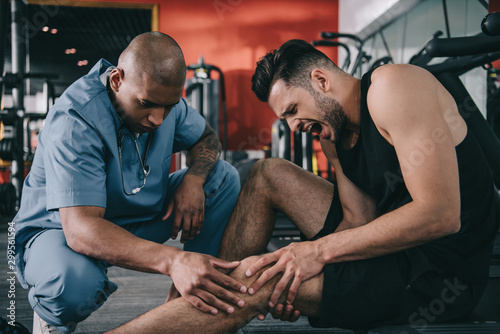 fototapeta na drzwi i meble african american doctor examining injured knee of screaming sportsman