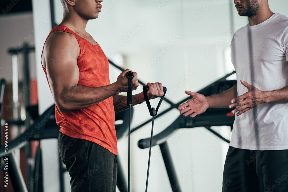 Fototapeta cropped view of trainer standing near african american sportsman exercising with expander