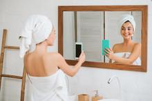 Beautiful Happy Woman In Towel Taking Selfie In Front Of Mirror In The Bathroom