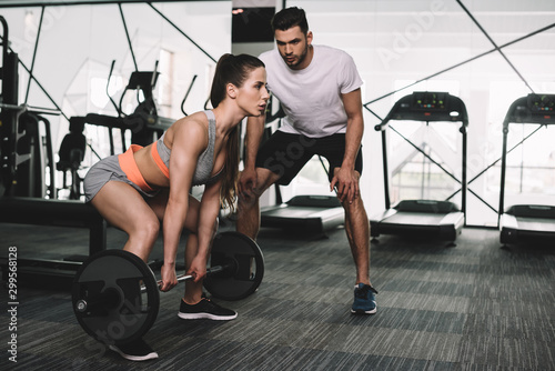 Deurstickers Fitness handsome trainer looking at athletic sportswoman lifting barbell