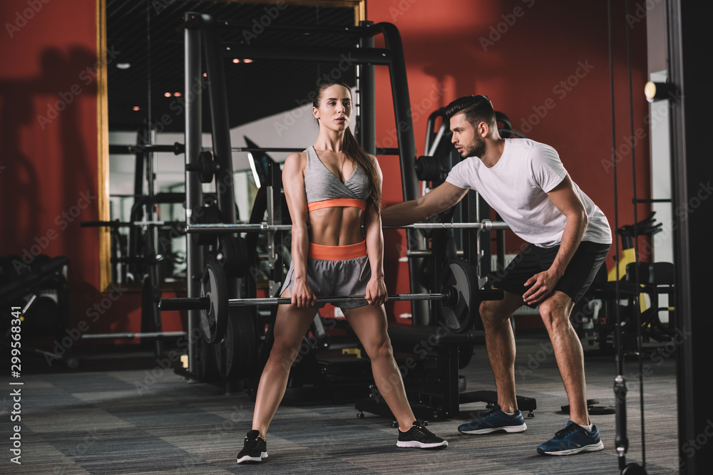 Fototapety, obrazy: handsome trainer supporting attractive sportswoman lifting barbell