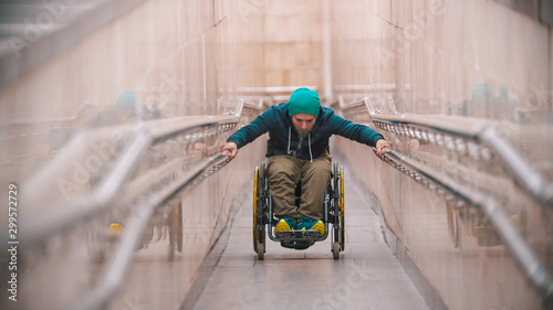 Disabled man in wheelchair getting up on the long special ramp leaning on the ra Canvas Print