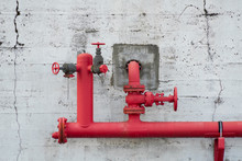 Red Pipes Coming Out Of A Wall...