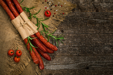 Thin Dry Smoked Polish Sausage on Wooden Background. Selective focus.