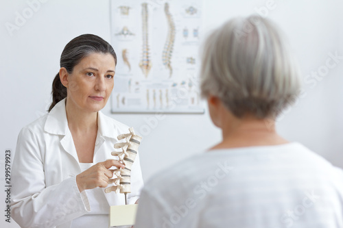 Fotografía Aging and back pain concept: doctor of orthopedics showing her senior patient a slipped disk on a backbone model