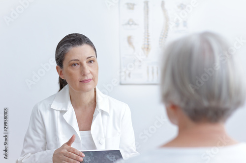 Fotomural  Female doctor with tablet computer showing her senior patient cat scan images of her degenerated vertebrae