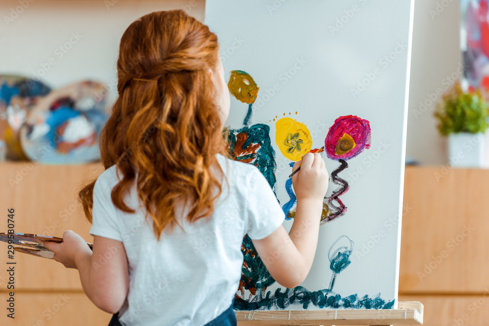 Fototapeta back view of redhead child painting on canvas in art school