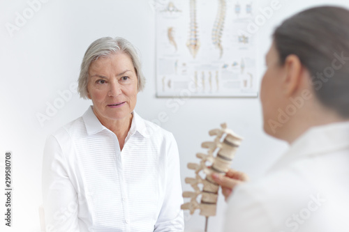 Obraz na plátne Aging and back pain concept: doctor of rheumatolgy showing her senior patient a slipped disk on a backbone model
