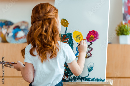 Obraz back view of redhead child painting on canvas in art school - fototapety do salonu