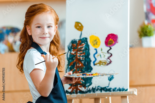 Photo smiling redhead child standing near painting on canvas in art school