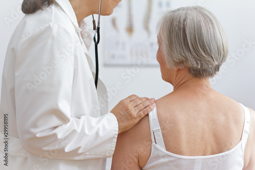 Health care concept: female doctor auscultating the heart of a senior patient with a stethoscope Wallpaper Mural