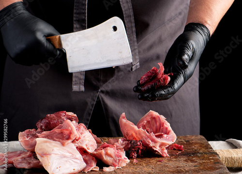 Obraz na plátně  chef in black latex chunks cuts into pieces raw rabbit meat on a brown wooden bo
