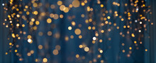 Holiday Illumination And Decoration Concept - Christmas Garland Bokeh Lights Over Dark Blue Background