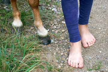 Bare feet of young girl standing near horse hooves close up outdoors on the country path. Comparison of human feet and horse hooves