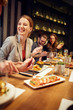 canvas print picture Charming smiling caucasian blonde sitting in restaurant, eating dinner and chatting with friend. In background are friends.