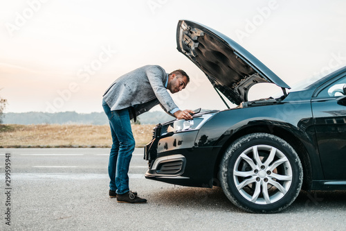 Fotografiet Elegant middle age business man trying to fix car breakdown or engine failure and waiting for towing service for help car accident on the road