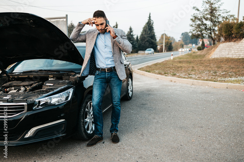 Photo Elegant middle age business man calling towing service for help on the road