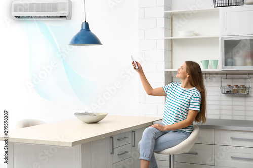 Young woman with air conditioner remote control at home Wallpaper Mural