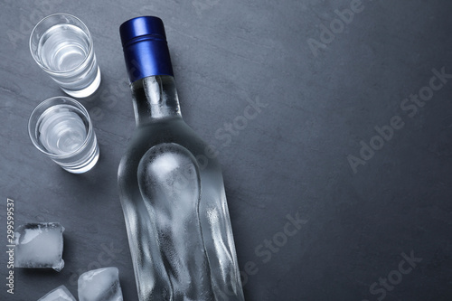 Recess Fitting Alcohol Bottle of vodka, ice cubes and shot glasses on black table, flat lay. Space for text