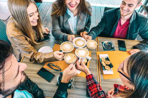 Top view of happy friends toasting cappuccino drink at coffee shop restaurant - Millennial people group having fun on breakfast together at fashion cafe bar - Friendship concept on vivid warm filter
