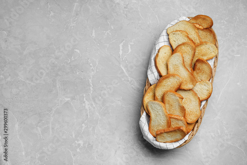 Fotografie, Obraz  Basket with toasted bread on grey table, top view. Space for text