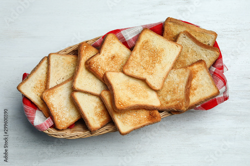 Obraz na plátně  Basket with toasted bread on white wooden table, top view