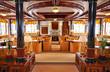 Leinwanddruck Bild - Elegante und luxuriöse Lounge Bar Aufenthaltsraum im Jugendstil auf Luxus Kreuzfahrtschiff Sea Cloud 2 mit orangenen Ledercouch und Ledersessel, Teakholz, Messing, Fenstern und Stuck Decke Intarsien
