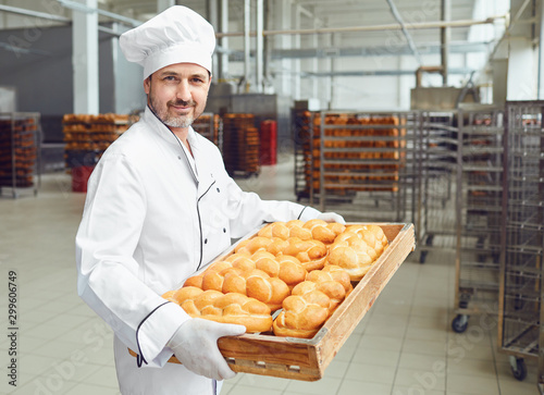 Papel de parede A baker in a bakery against the shelves of bread.