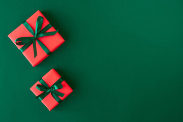 Red gift boxes on green background. Christmas card. Flat lay. Top view with space for text