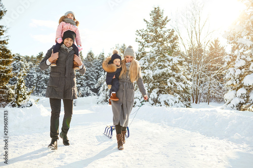 Happy family sledding in the park in winter.