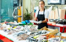Glad Female Fishmonger Offering Fresh Sea Bass
