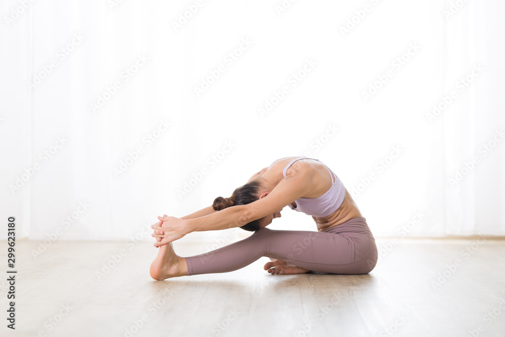 Fototapety, obrazy: Portrait of gorgeous active sporty young woman practicing yoga in studio. Beautiful girl practice Janushiransa with Paschimotthanasana, head to knee with streching yoga pose.