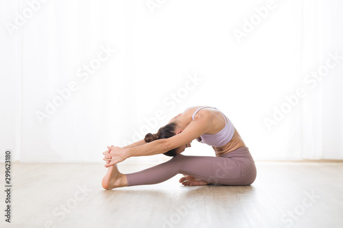 Foto auf Gartenposter Individuell Portrait of gorgeous active sporty young woman practicing yoga in studio. Beautiful girl practice Janushiransa with Paschimotthanasana, head to knee with streching yoga pose.