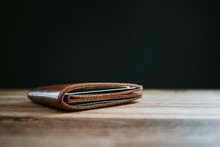 Brown Leather Wallet On A Wooden Table With Black Background. Copy Space.