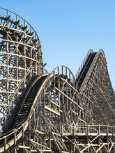 A Large Wooden Roller Coaster At An Amusement Park. Thrill