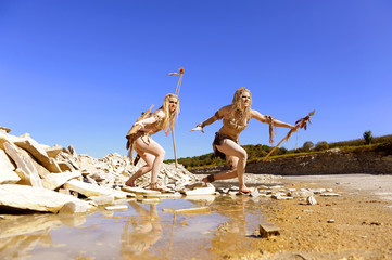 Two girls are dressed as neanderthal warriors. They are  covered with mud,filth and dirt and are seen in a stone quarry.