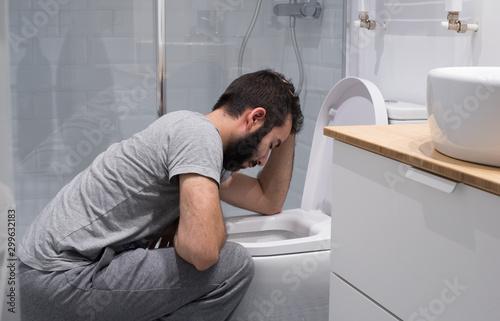 Foto Hombre en el baño intentando vomitar en el inodoro