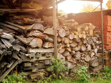 Raw Firewood Logs Stacked For Winter. Rural Life And Source Of Energy.Sun Flare.