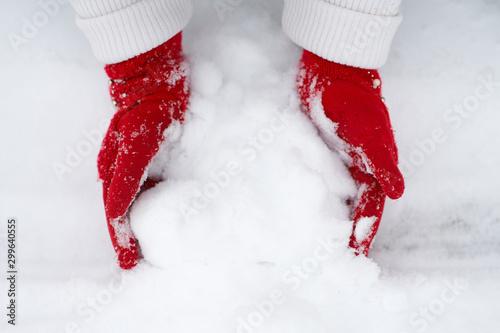 Fototapeta Girl's hands in red gloves making snowball