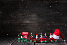 Toy Of Christmas Train With Santa Claus Hat On Wooden Rustic Background