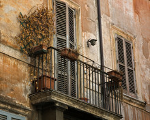 Old Roman Balcony With Iron Railing On A Rustic, Weathered Building