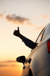 Man showing thumbs up/making Like / Ok sign with hand from car window with sunset sky, relaxing, enjoying road trip and feeling the air and freedom. Toward adventure, vacation