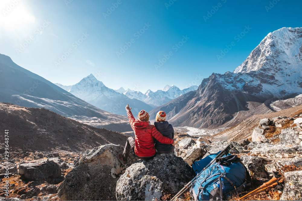 Fototapeta Couple having a rest on Everest Base Camp trekking route near Dughla 4620m. Backpackers left Backpacks and trekking poles and enjoying valley view with Ama Dablam 6812m peak  and Tobuche 6495m