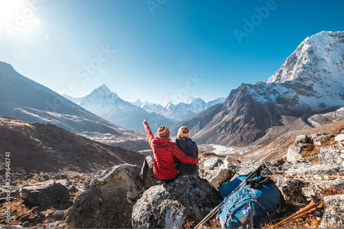 Fototapeta Couple having a rest on Everest Base Camp trekking route near Dughla 4620m. Backpackers left Backpacks and trekking poles and enjoying valley view with Ama Dablam 6812m peak  and Tobuche 6495m obraz