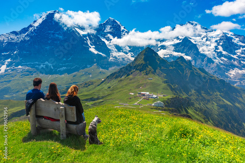 Foto Tourists admire Eiger, Monch and Jungfrau mountains from summit of mountain Mannlichen, popular viewpoint in Swiss Alps, Switzerland