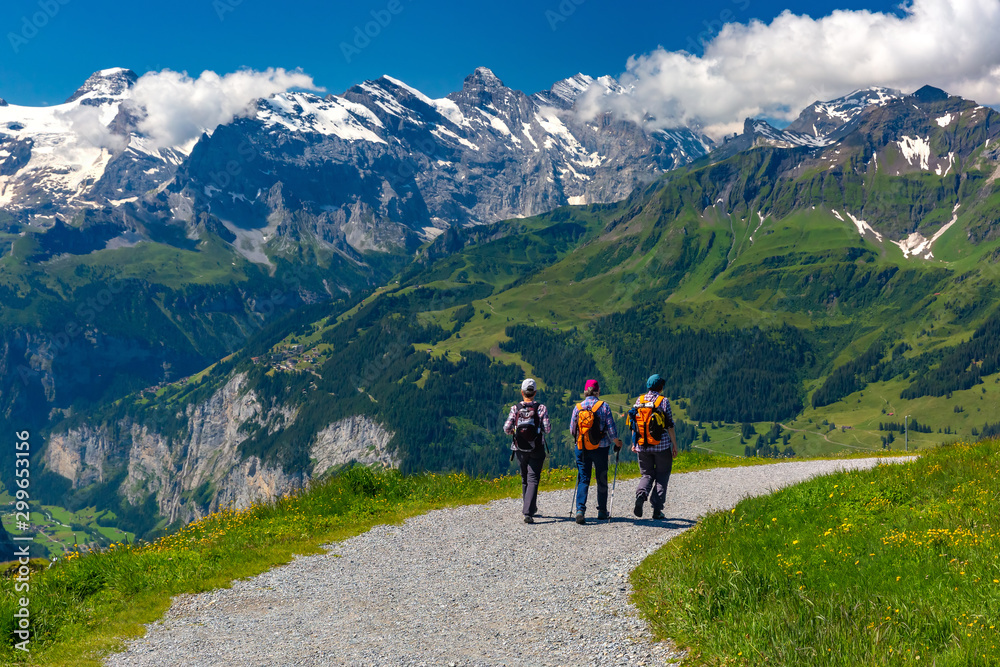 Fototapety, obrazy: Tourists on hiking trail on mountain Mannlichen, popular viewpoint in Swiss Alps, Switzerland.