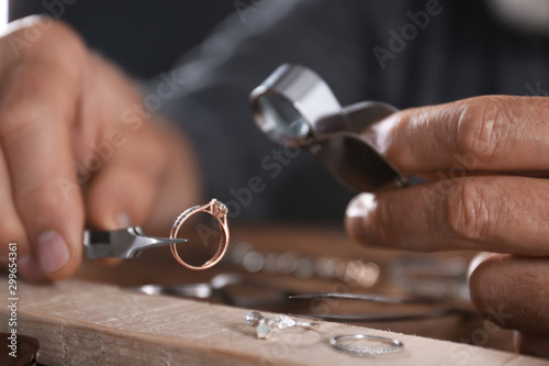 Male jeweler examining diamond ring in workshop, closeup view Canvas Print