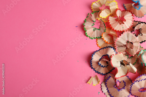 Pencil shavings on pink background, top view. Space for text