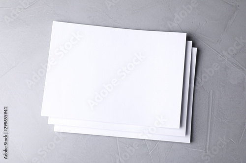 Poster Fleur Blank paper sheets on light grey stone background, top view. Mock up for design